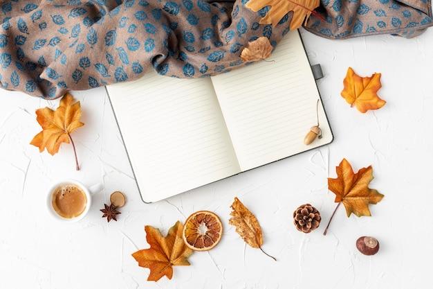 Caderno vazio ao lado de folhas amarelas