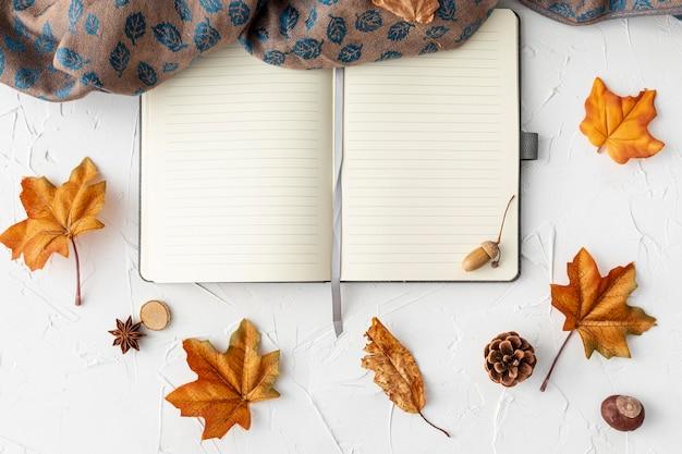 Caderno vazio ao lado de folhas e pano