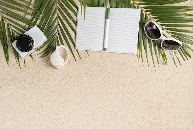 Caderno vazio, câmera pequena e óculos de sol brancos na areia e brunches de palmeira verde tropical, espaço de cópia, conceito de férias tropicais de viagem