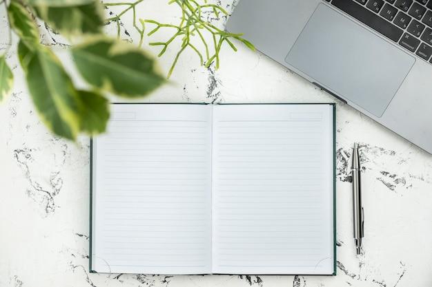 Caderno vazio com caneta e laptop. vista do topo