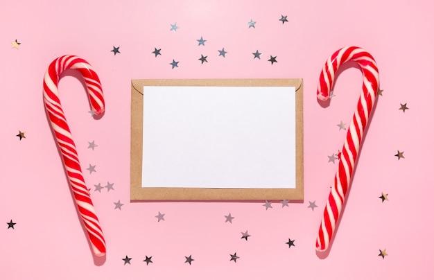 Caderno vazio com doces de natal vermelhos e estrelas de confetes derrama sobre um fundo rosa pastel, vista superior. postura plana. ano novo de férias, saudação ou conceito de boas notícias. modelo de maquete. bloco de notas em branco