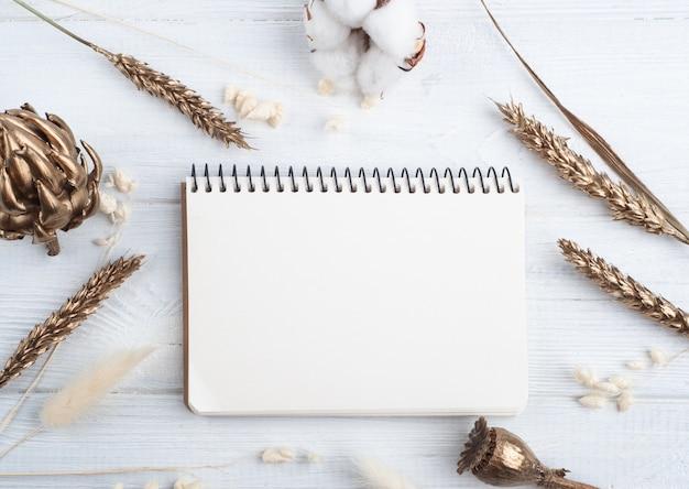 Caderno vazio com flores e sementes douradas secas