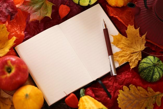 Caderno vazio com folha de bordo, maçãs e abóboras
