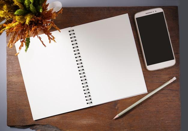 Caderno vazio com lápis, smartphone e flor seca na mesa de madeira.