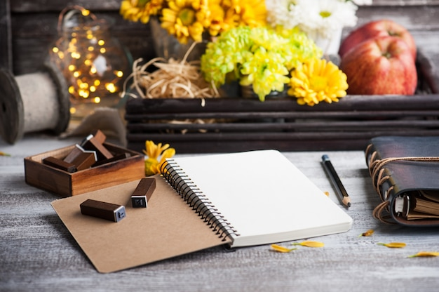 Caderno vazio com luzes acesas e crisântemo