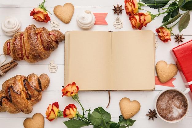 Caderno vazio com papel artesanal aberto na mesa de madeira branca com croissants e padaria