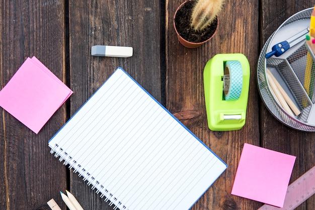 Caderno vazio com papelaria na mesa de madeira