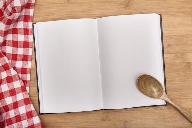 Caderno vazio de receitas com colher e toalha de mesa na mesa de madeira
