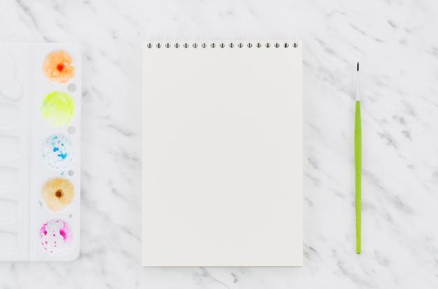Caderno vazio de vista superior com material de pintura