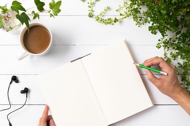 Caderno vazio deitado com plantas