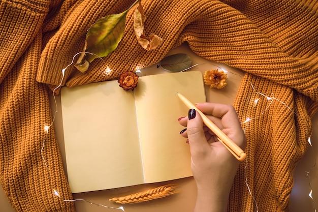 Caderno vazio e com mão de mulher