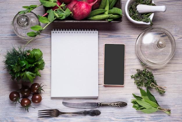 Caderno vazio e smartphone para o seu texto, em fundo madeira