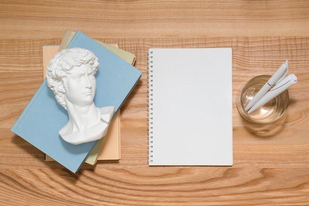 Caderno vazio na mesa de madeira com livros e uma pequena escultura de gesso de david