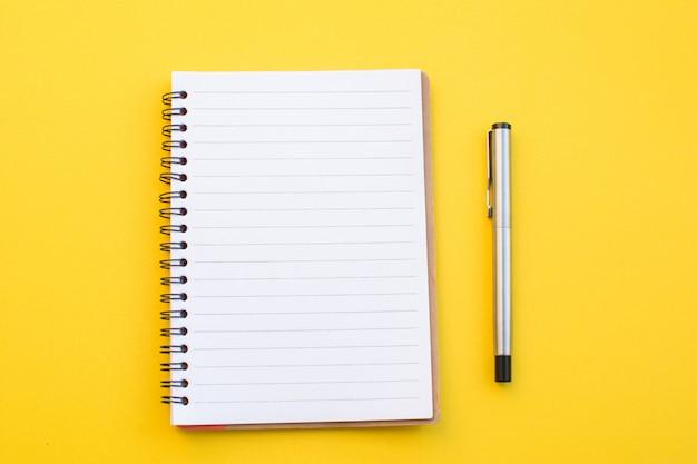 Caderno vazio no fundo amarelo com conceito da escola.