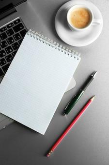 Caderno vazio no teclado do laptop, na superfície clara