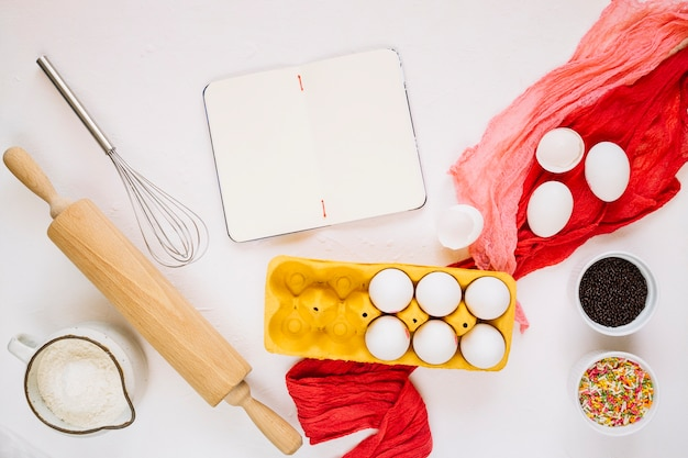 Caderno vazio perto de ingredientes e ferramentas de cozinha