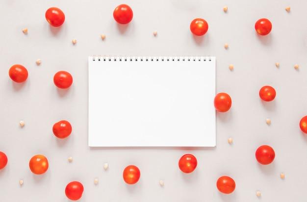 Caderno vazio rodeado de tomate cereja