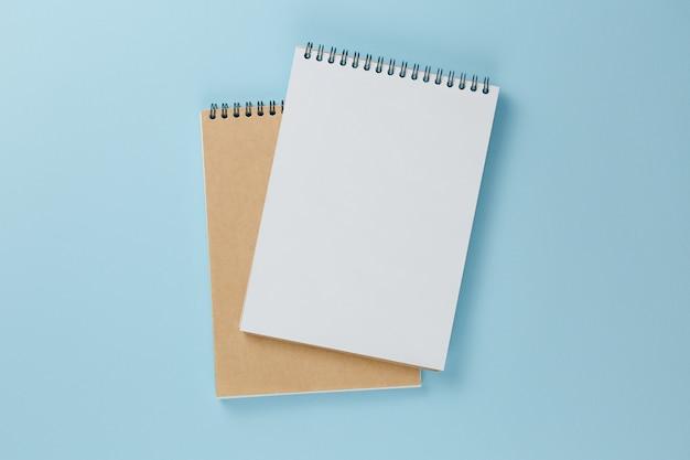 Caderno vazio, vista superior da parede azul clara, mesa de escritório plana