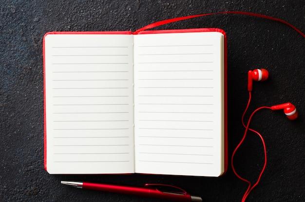 Caderno vermelho aberto vazio com caneta vermelha e fones de ouvido no fundo escuro