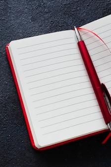 Caderno vermelho aberto vazio com caneta vermelha em fundo escuro