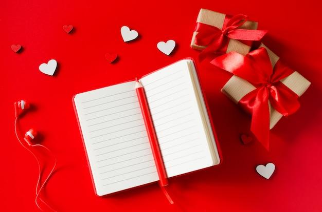 Caderno vermelho, caixas de presente, corações de madeira, lápis e fones de ouvido.