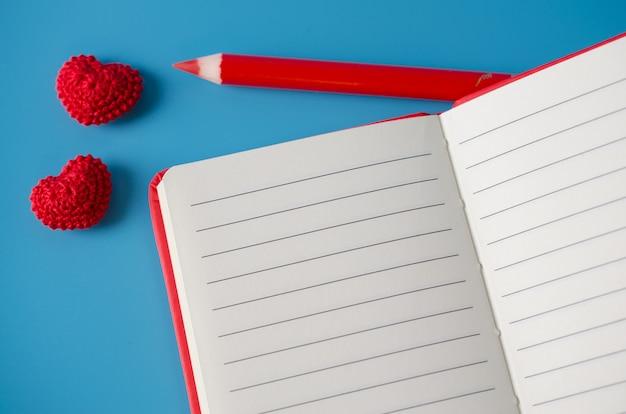 Caderno vermelho com lápis e dois corações de malha. cartão para dia dos namorados.