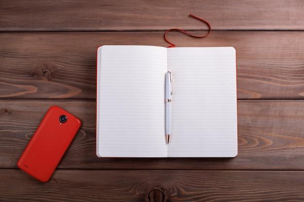 Caderno vermelho e um smartphone.