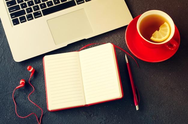 Caderno vermelho em branco, computador portátil, fones de ouvido e xícara de chá.