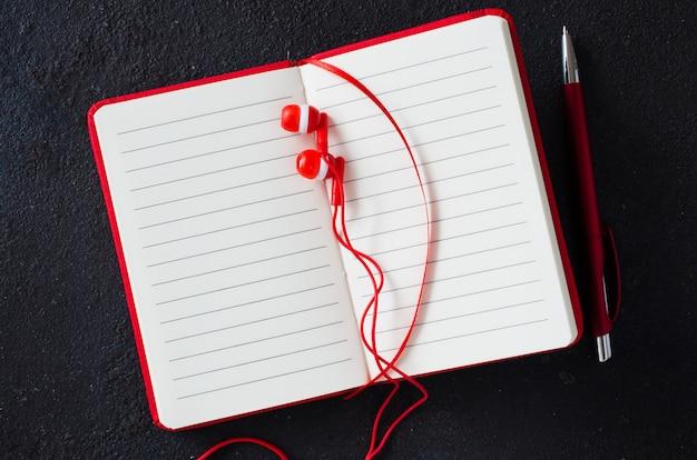 Caderno vermelho vazio com caneta vermelha e fones de ouvido