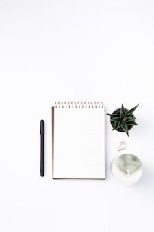 Caderno vertical com uma panela, uma planta e uma vela