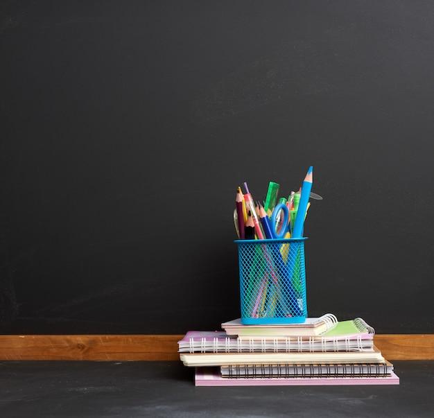 Caderno, vidro de papelaria azul com lápis de madeira multicoloridos