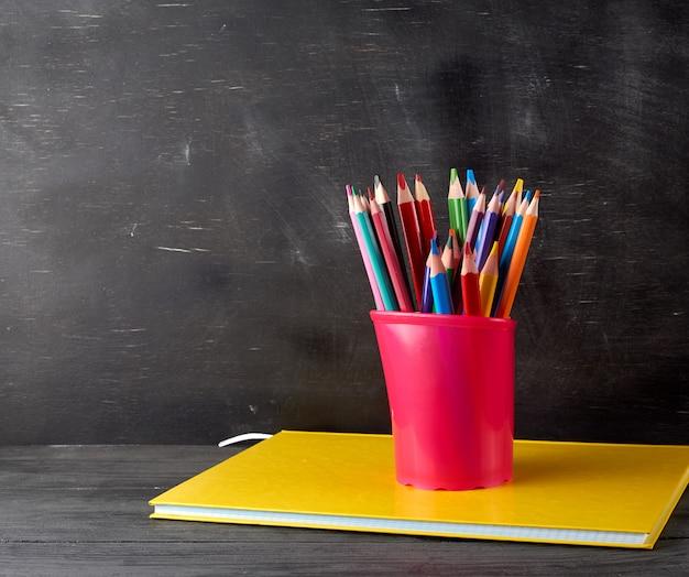 Caderno, vidro de papelaria preto com lápis de madeira multicoloridos