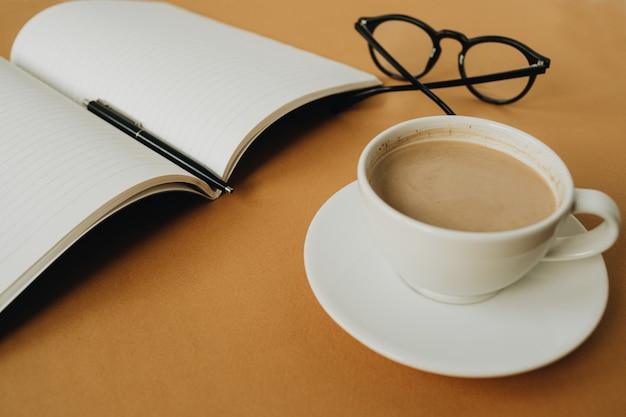 Caderno, xícara de café, copos na superfície de gengibre