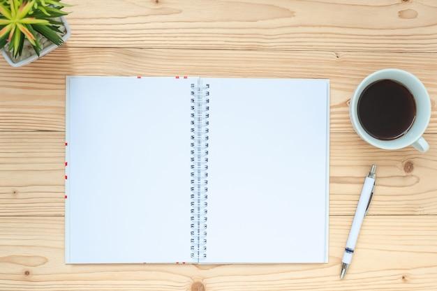 Caderno, xícara de café preto, caneta e copos na mesa