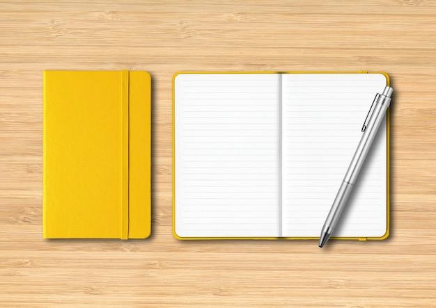 Cadernos amarelos fechados e abertos com uma caneta isolada em madeira