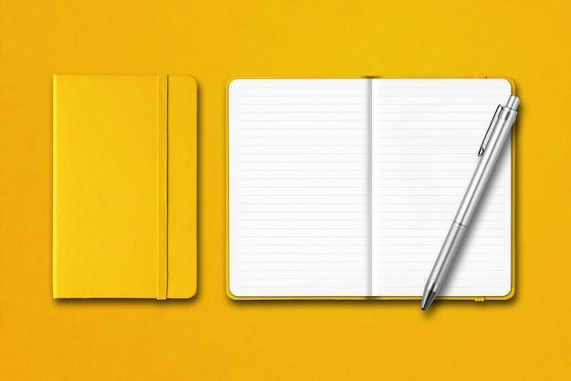 Cadernos amarelos fechados e abertos com uma caneta isolada