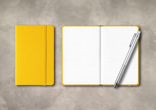 Cadernos amarelos fechados e abertos com uma caneta