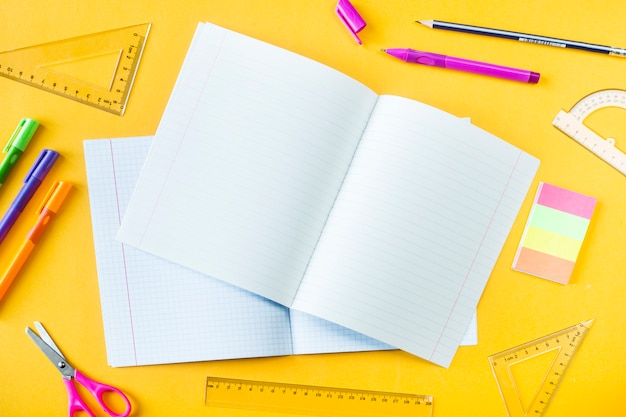 Cadernos, canetas, lápis e réguas em um fundo amarelo