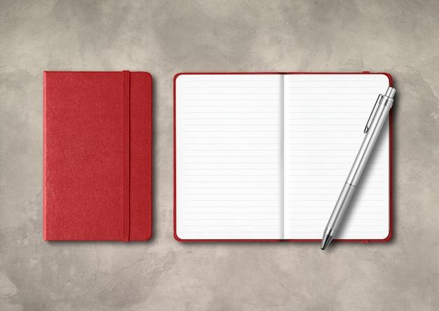 Cadernos com forro vermelho escuro fechados e abertos com uma caneta. maquete isolada em fundo de concreto