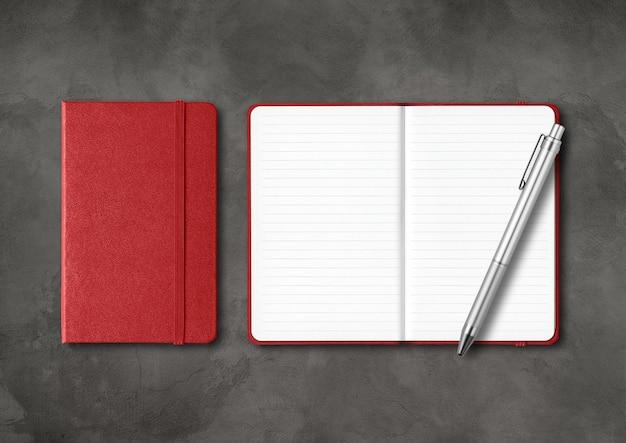 Cadernos com forro vermelho escuro fechados e abertos com uma caneta. maquete isolada em fundo preto de concreto