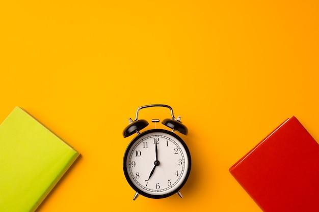 Cadernos de capa dura de três cores e despertador em vista superior com fundo amarelo