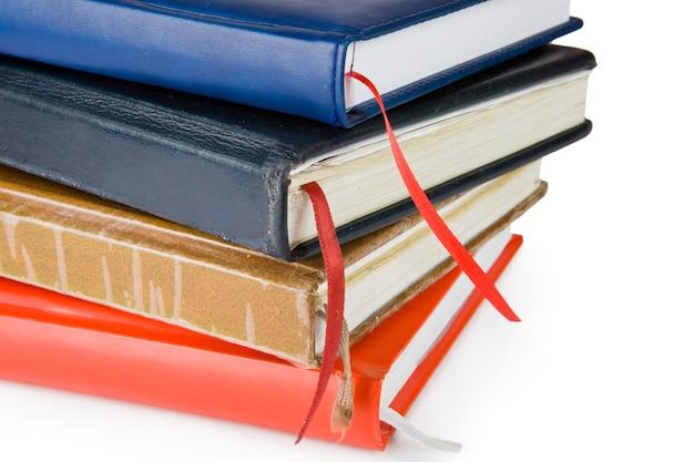 Cadernos de couro coloridos fechados isolados no fundo branco com traçado de recorte.