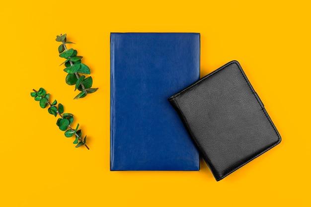 Cadernos de couro preto e azul na área de trabalho amarelo do escritório, conceito de espaço de trabalho comercial com flores secas, foto plana e vista superior