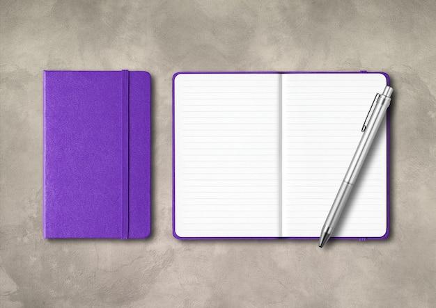 Cadernos de notas roxas fechadas e abertas com uma caneta. maquete isolada em fundo de concreto