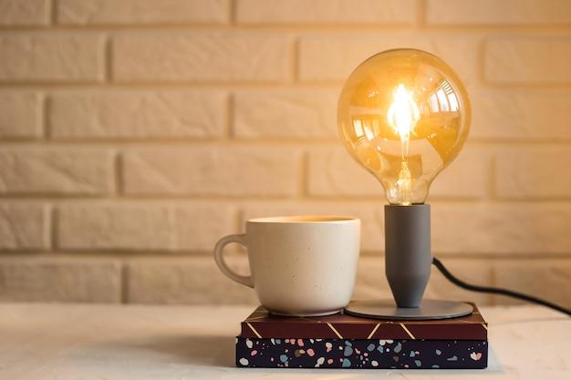 Cadernos de trabalho e planadores na área de trabalho em que há uma lâmpada e uma xícara de café
