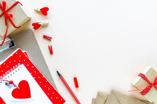 Cadernos e envelopes para a escola ou escritório em vermelho sobre uma mesa branca com espaço de cópia.