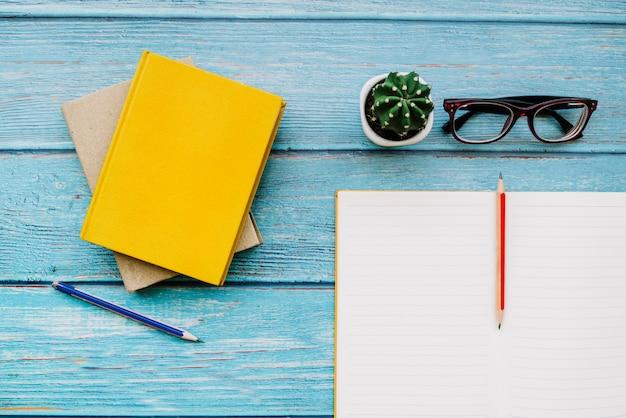 Cadernos e lápis em uma mesa de madeira
