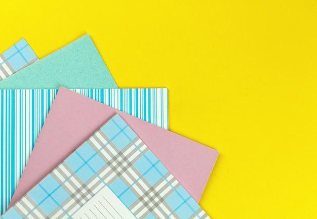 Cadernos escolares na área de trabalho amarela brilhante, foto de fundo do conceito de escola primária com espaço de cópia