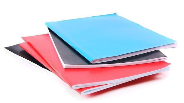 Cadernos escolares sobre uma mesa branca.