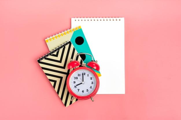 Cadernos geométricos e despertador na rosa estacionário, de volta à escola conceito flat lay